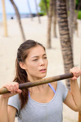 Exercise woman training arms on pull-up bar