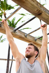 Workout man working out arms on brachiation ladder