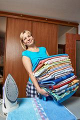 Happy housewife with big stack of towels