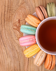 Colorful French Macarons with Cup of Tea on wooden background