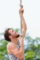 Crossfit man doing rope climb workout climbing