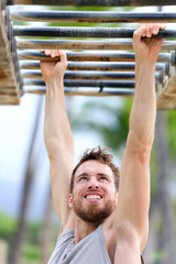 Fit man cross training outside on monkey bars