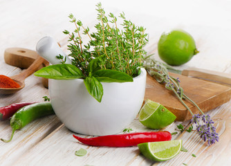 Fresh herbs and  chili peppers on  wooden background.