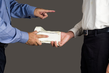 Man point and hand over envelope full of money to another person
