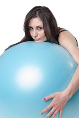 Young athletic woman with blue exercise ball