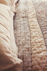 Close up of contemporary luxury bed quilt cover and pillows