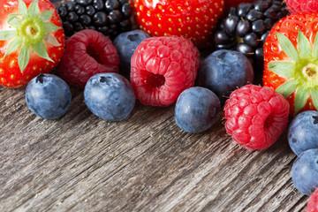 assorted fresh juicy berries on wooden background, horizontal