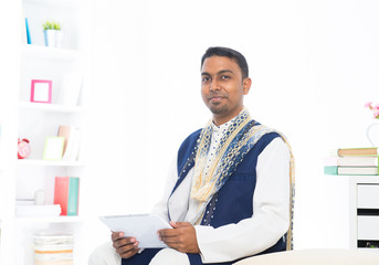 indian male with tradtional dresss and tablet computer