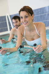 Couple in pool doing aquabike training