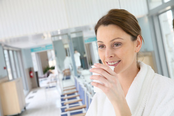Woman in bathrobe drinking hot tea in spa center