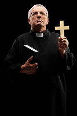 Mature priest holding a cross and looking up