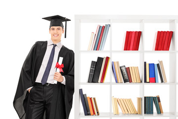 Graduate holding diploma and leaning on bookshelf