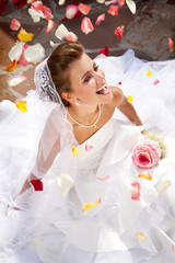 Happy Laughing Bride Sitting Outdoors on the Floor with Petals