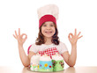 happy little girl cook with sweet cake and ok hand sign