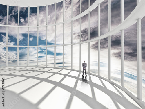Fototapeta businessman standing in office and looking at sky in window
