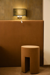 Luxury hotel room detail, chair, lamp and leather walls