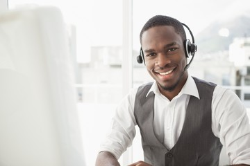 Happy businessman with headset interacting