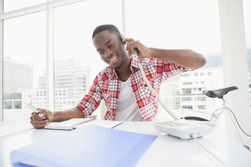 Happy businessman phoning and taking notes