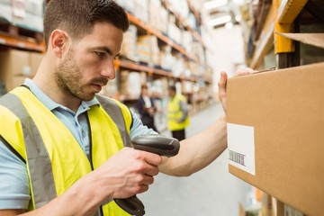 Warehouse worker scanning barcodes on boxes
