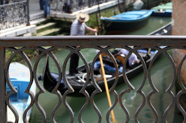 Venetian gondolier on his gondola, Venice, Italy