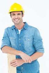 Happy carpenter leaning on wooden plank