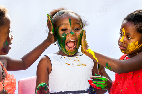 African kids painting friends face. - 77055268