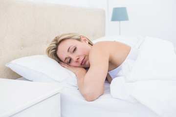 Thoughtful blonde woman lying in bed