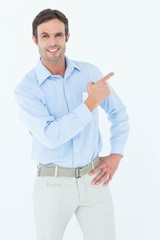 Confident businessman pointing at copy space