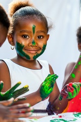 Close up of african girl painting with friends.