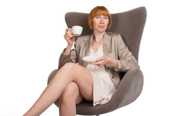 Young lady in office style on modern chair with a cup of coffee
