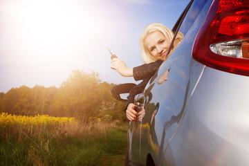 Frau hält Autoschlüssel aus dem Autofenster
