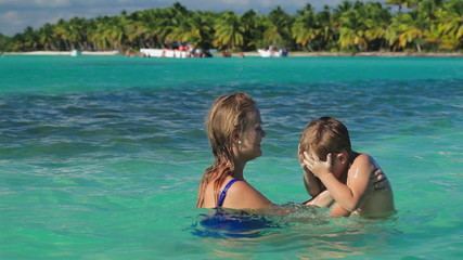 Mother and son playing in clear sea water