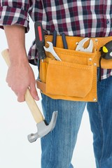 Repairman wearing tool belt while holding hammer
