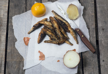 Fried smelts on white paper with lemon, onion and potato