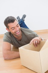 Smiling man open a moving box at home