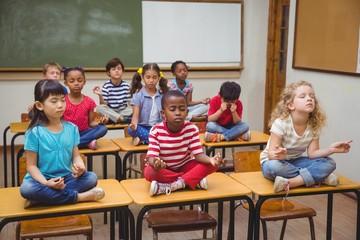 Pupils meditating in lotus position on desk in classroom
