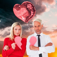 Couple not talking holding two halves of broken heart