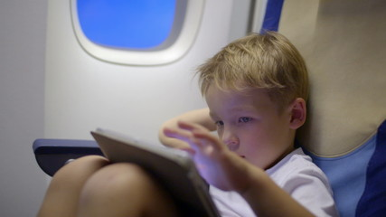 Bored or tired boy in plane using tablet computer