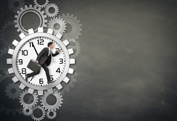 Businessman running in Wheel with Clock
