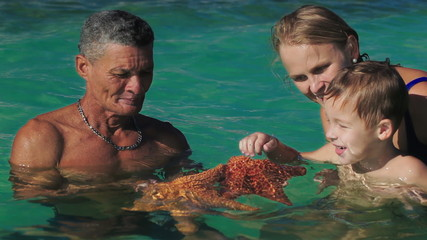 Man showing tourists two big starfish