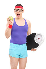 Nerdy guy eating apple and holding a weight scale