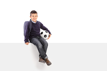 Schoolboy holding soccer ball seated on a panel