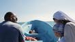 Man turning a boat while talking to passenger