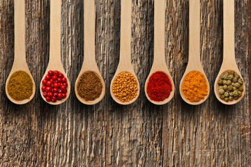Different spices in the spoons on wooden surface