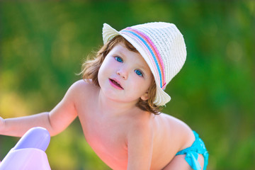 Baby kid girl with hat in summer on green field
