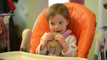 Little girl eating a piece of bread