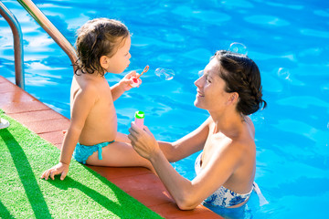 Baby girl blowing soap ballons with mother in pool