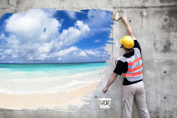 worker with paint brushes drawing summer beach on the wall