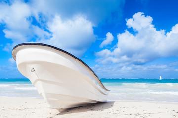 White pleasure motor boat lays on sandy beach