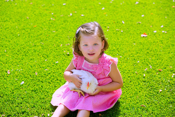 Toddler kid girl with white hen in green turf